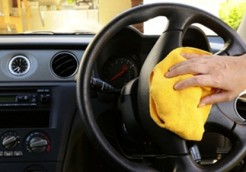 Woman's nand with microfiber cloth polishing steering wheel of an SUV car